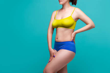 Plus size model in colored underwear on blue background, body positive concept