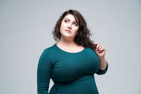 Plus size fashion model in green dress, fat woman on gray studio background, body positive concept