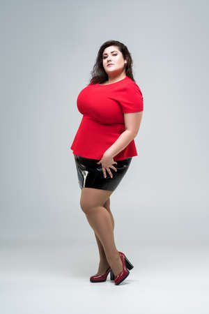 Plus size fashion model in red blouse and black skirt, fat woman on gray studio background, body positive concept