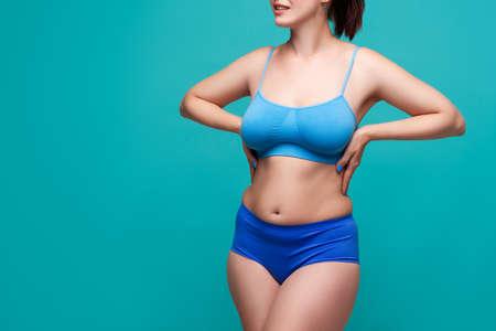 Plus size model in blue underwear on turquoise background, body positive concept Standard-Bild