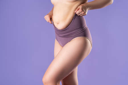 Fat woman in corrective panties, flabby belly after pregnancy, overweight female body on purple background, studio shot Imagens