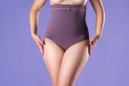 Woman in corrective panties, female body in shapewear on purple background, studio shot Фото со стока