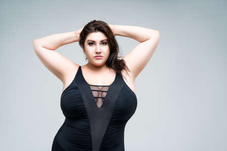 Sexy plus size fashion model in black one-piece swimsuit, fat woman in lingerie on gray background, body positive concept
