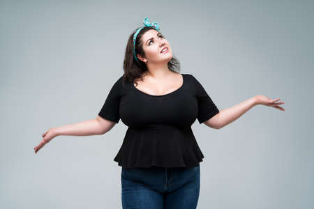 Happy plus size fashion model in black blouse with deep neckline, fat woman on gray studio background, body positive concept