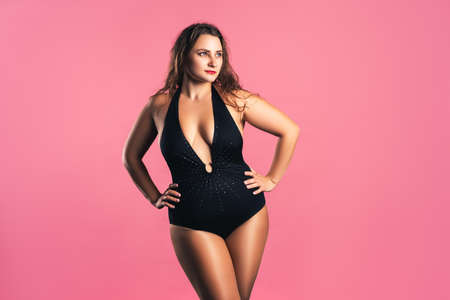 Sexy plus size fashion model in black one-piece swimsuit, fat woman in lingerie on pink background, body positive concept