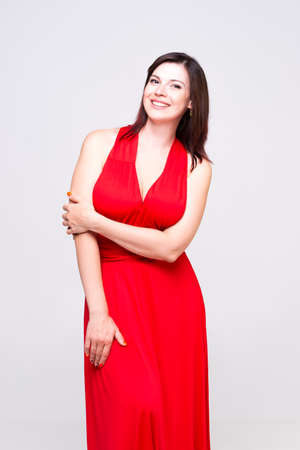 Happy woman in red dress with deep neckline in studio on gray background, Banque d'images