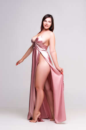 Sexy woman in pink dress with deep neckline in studio on gray background, full-length portrait
