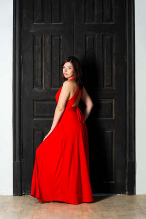 Beautiful sexy woman in red dress in interior, sensual portrait