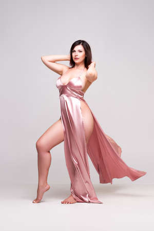 Sexy woman in pink dress with deep neckline in studio on gray background.