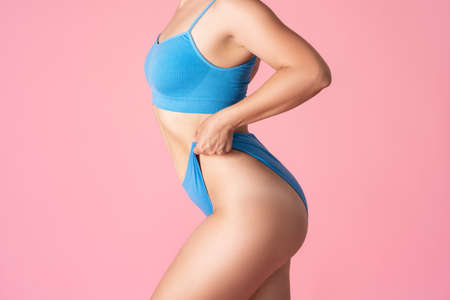 Slim sexy woman in blue underwear on pink background, body care concept