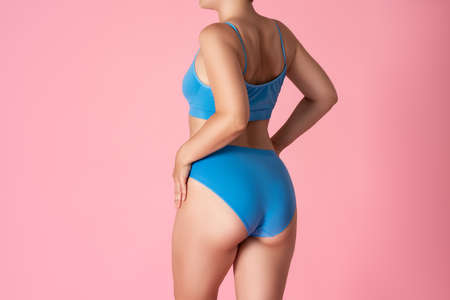 Slim woman in blue underwear on pink background, body care concept