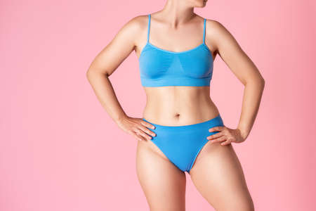 Slim woman in blue underwear on pink background, body care concept Stock Photo