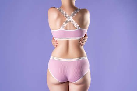 Slim woman in pink underwear on purple background, body care concept Zdjęcie Seryjne