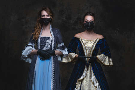 Two women in renaissance dress, face mask and gloves on abstract dark background, old and new concept