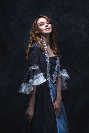 Happy beautiful woman in renaissance dress on abstract dark background, studio shot Zdjęcie Seryjne
