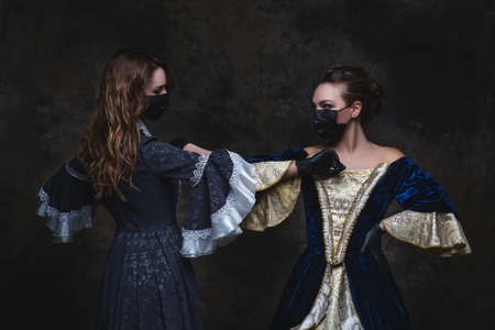 Two women in renaissance dress, face mask and gloves greeting bumping elbows on abstract dark background, old and new concept Zdjęcie Seryjne