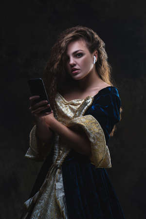 Beautiful woman in renaissance dress listens to music in wireless headphones on abstract dark background, old and new concept