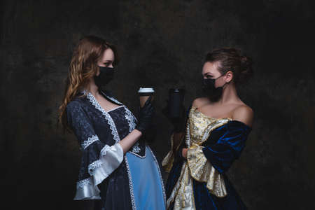 Two women in renaissance dress drinking coffee on abstract dark background, old and new concept Zdjęcie Seryjne