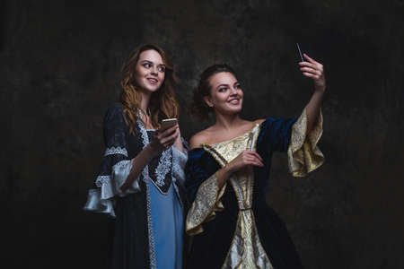 Two happy women in renaissance dress taking selfie on smartphone, old and new concept, abstract dark background