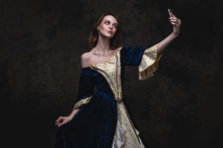 Beautiful woman in renaissance dress taking selfie on smartphone, old and new concept, abstract dark background