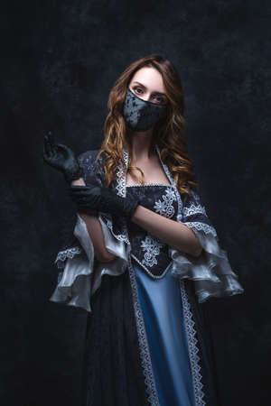 Beautiful woman in renaissance dress, face mask and gloves on abstract dark background, old and new concept