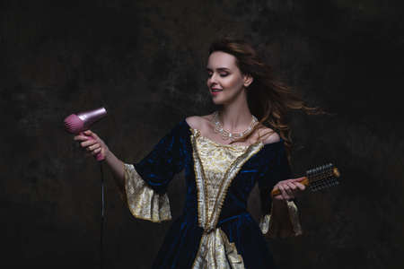 Beautiful woman in renaissance dress styling her hair with a hair dryer on abstract dark background, studio shot