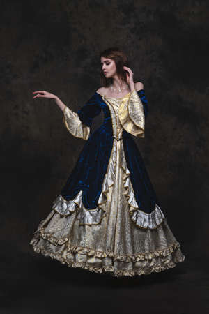 Beautiful woman in renaissance dress on abstract dark background, full length portrait