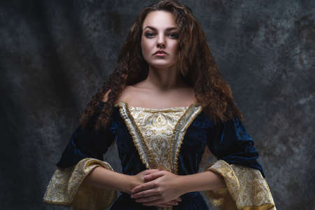 Beautiful woman in renaissance dress on abstract dark background, studio shot