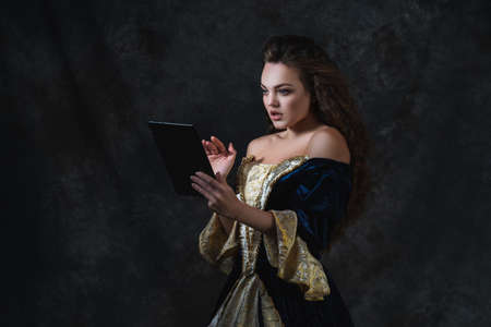 Beautiful woman in renaissance dress uses tablet on abstract dark background, old and new concept