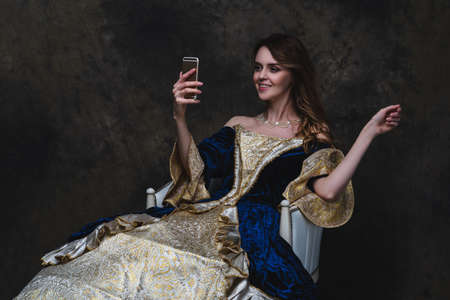 Beautiful happy woman in renaissance dress taking selfie on smartphone, old and new concept, abstract dark background