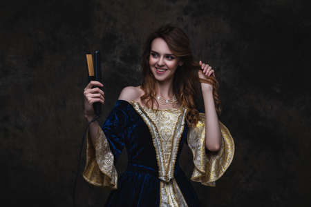Happy beautiful woman in renaissance dress styling her hair with a curling iron on abstract dark background, studio shot Zdjęcie Seryjne