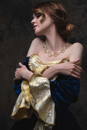 Beautiful sexy woman in renaissance dress on abstract dark background, studio shot