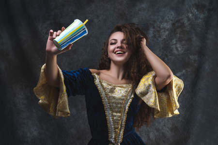 Happy beautiful woman in renaissance dress with cocktail on abstract dark background, old and new concept Zdjęcie Seryjne