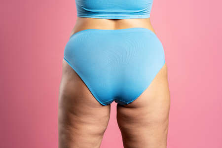 Overweight woman with fat hips and buttocks, obesity female body on pink background, studio shot Zdjęcie Seryjne