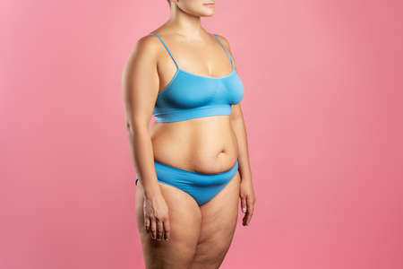 Fat woman in blue underwear on pink background, overweight female body, studio shot
