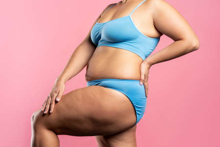 Fat woman in blue underwear on pink background, overweight female body, studio shot with copy space Zdjęcie Seryjne