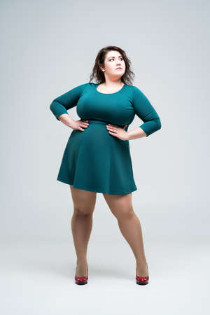 Sexy plus size fashion model in green dress, fat woman on gray background, body positive concept, full length portrait