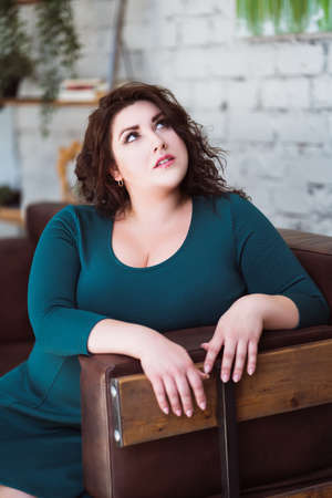 Plus size fashion model in green dress in the interior, fat woman at home, body positive concept