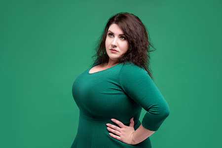 Plus size fashion model in green dress, fat woman on green studio background, body positive concept