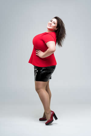 Happy plus size fashion model in red blouse and black skirt, fat woman on gray studio background, body positive concept