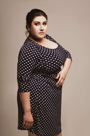 Plus size fashion model in polka dot dress, fat woman on studio background, body positive concept