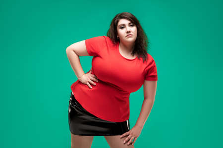 Plus size fashion model in red blouse, fat woman on green studio background, body positive concept