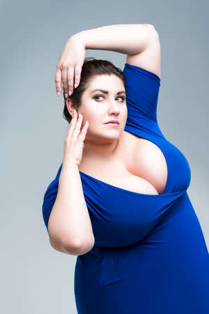 Sexy plus size fashion model in black blouse with deep neckline, fat woman on gray studio background, body positive concept Zdjęcie Seryjne