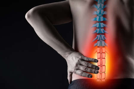 Pain in the spine, man with backache on black background, intervertebral hernia or disc injury concept