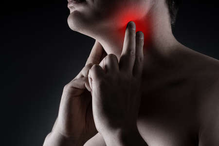 Sore throat, men with pain in neck on black background, painful area highlighted in red Stock Photo