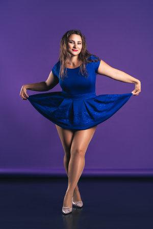 Happy plus size model in blue dress on purple background, body positive concept