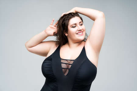 Sexy plus size fashion model in black one-piece swimsuit, fat woman in lingerie on gray background, body positive concept Imagens