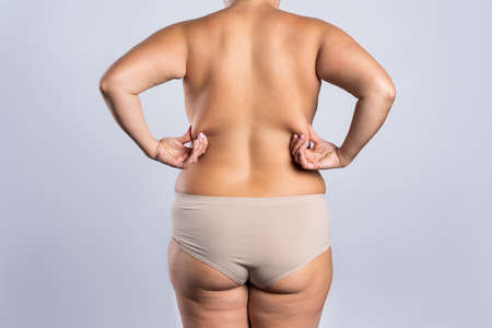 Overweight woman with fat hips and buttocks, obesity female body on gray background, studio shot Imagens