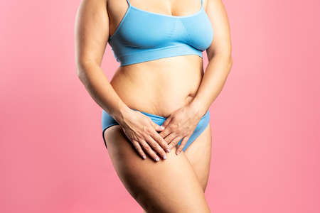 Fat woman in blue underwear on pink background, overweight female body, studio shot with copy space