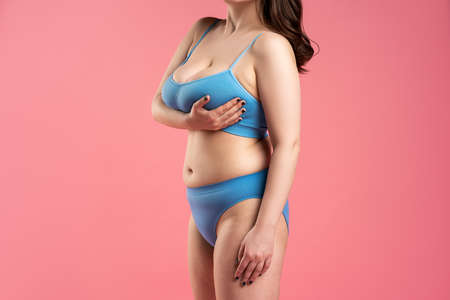 Fat woman with very large in blue underwear on pink background, body care concept, studio shot